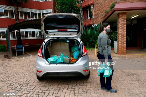 Adele Oosthuizen from Kindness Like Confetti a non-governmental organisation carry food parcels as she waits to give them to stranded University of...
