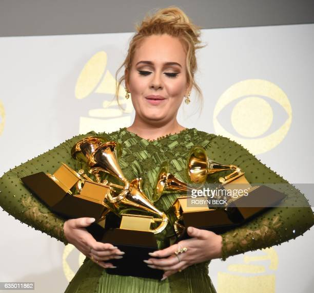 Adele poses in the press room with her trophies including the top two Grammys of Album and Record of the Year for her blockbuster hit 'Hello' and the...