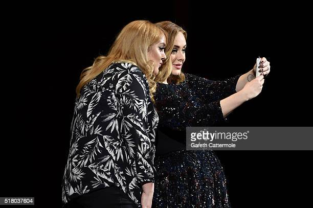 Adele poses with a fan for a selfie at Genting Arena on March 29 2016 in Birmingham England