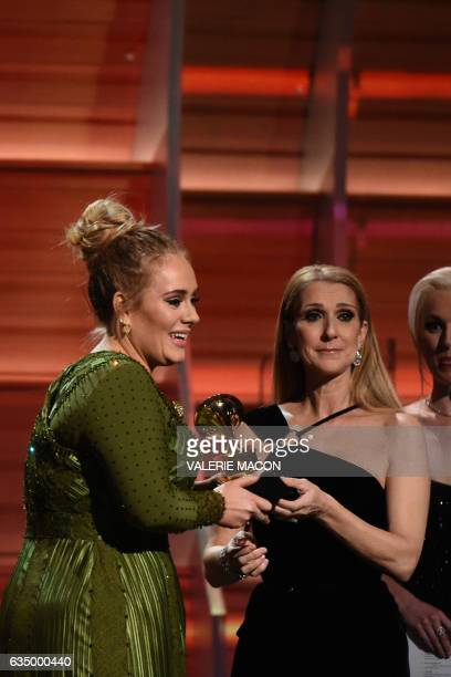 Adele receives the Grammyfor best song of the year from Celine Dion during the 59th Annual Grammy music Awards on February 12 in Los Angeles...