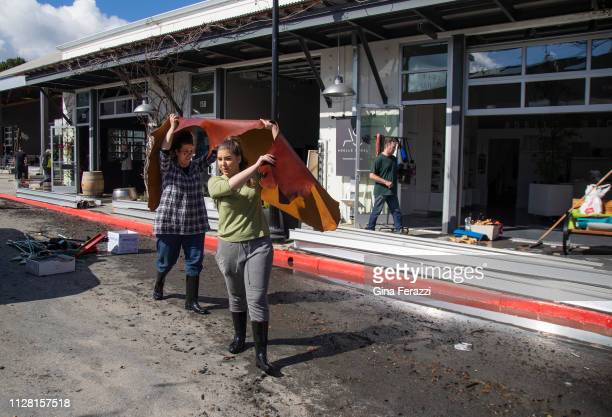 Adelle Stoll left and her daughter Valentina carry a wet piece of leather fabric after their shop was flooded at The Barlow market district after the...