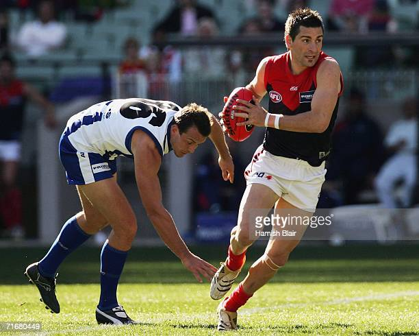 Adem Yze for Melbourne runs clear of Shannon Watt for the Kangaroos during the round 20 AFL match between the Kangaroos and the Melbourne Demons at...