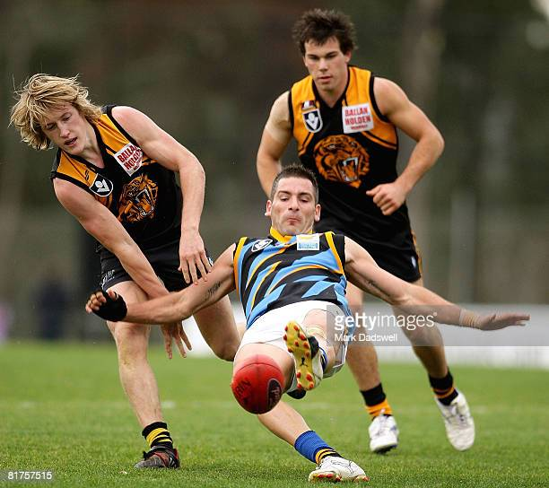 Adem Yze of Sandringham kicks clear of his tackler during the round 12 VFL match between the Werribee Tigers and the Sandringham Zebras at the...