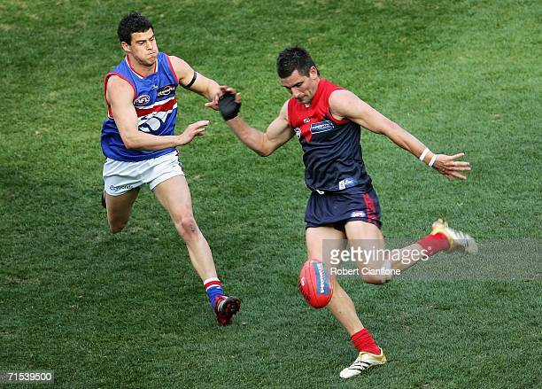 Adem Yze of the Demons gets his kick away from an advancing Lindsay Gilbee of the Bulldogs during the round 17 AFL match between the Melbourne Demons...