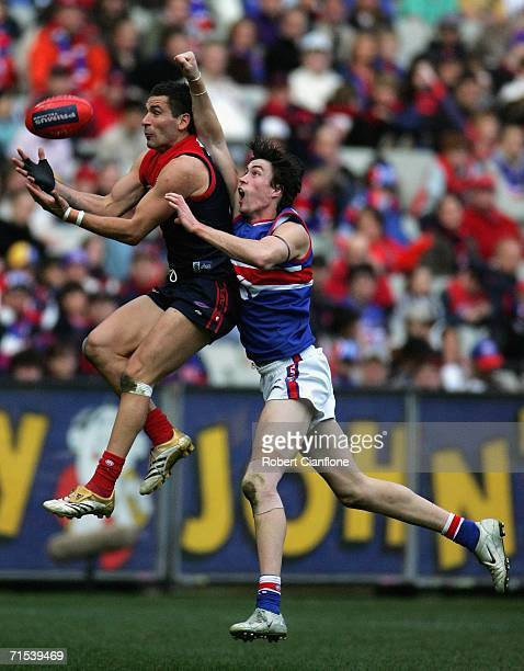 Adem Yze of the Demons gets the ball ahead of Cameron Wright of the Bulldogs the round 17 AFL match between the Melbourne Demons and the Western...
