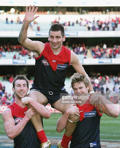 Adem Yze of the Demons is chaired off the ground by teammates Brock McLean and Colin Sylvia after playing his 250th match the round 17 AFL match...