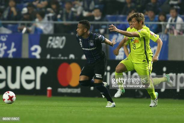 Ademilson of Gamba Osaka and Tsukasa Shiotani of Sanfrecce Hiroshima compete for the ball during the JLeague J1 match between Gamba Osaka and...