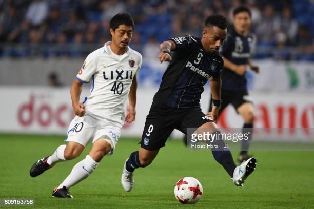 Ademilson of Gamba Osaka controls the ball under pressure of Mitsuo Ogasawara of Kashima Antlers during the JLeague J1 match between Gamba Osaka and...