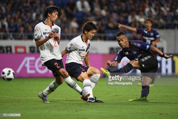 Ademilson of Gamba Osaka scores the winner under the challenge from Sei Muroya and Masato Moroishige of FC Tokyo during the J.League J1 match between...
