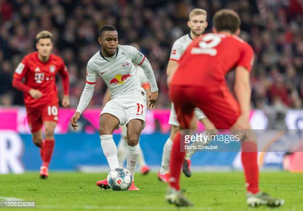 Ademola Lookman of RB Leipzig is challenged by Benjamin Pavard of FC Bayern Muenchen during the Bundesliga match between FC Bayern Muenchen and RB...