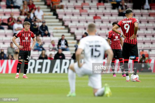 Aden Baldwin of MK Dons takes the knee as bournemouth's Gavin Kilkenny, Lloyd Kelly and Dominic Solanke choose to stand during the Carabao Cup 1st...
