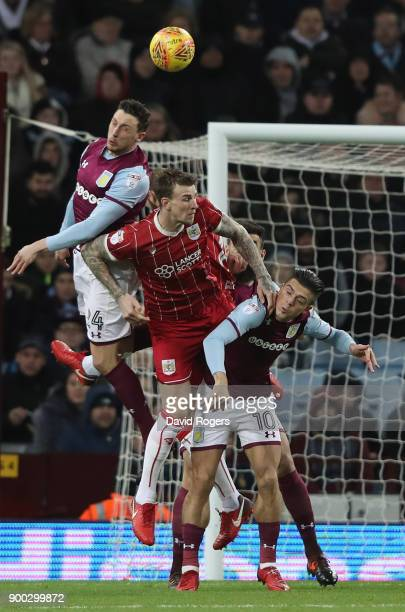 Aden Flint of Bristol City is challenged by Tommy Elphick and Jack Grealish during the Sky Bet Championship match between Aston Villa and Bristol...