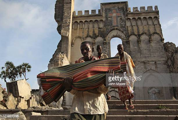 Aden Madow carries the body of Hamza Ali Faysal from a camp of displaced Somalis within the rubble of the Cathedral of Mogadishu on August 13 2011 in...