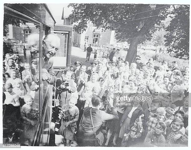 Adenauer Cheered West Germany School children and adults cheer West German chancellor Konrad Adenauer as he looks from a window of his special...