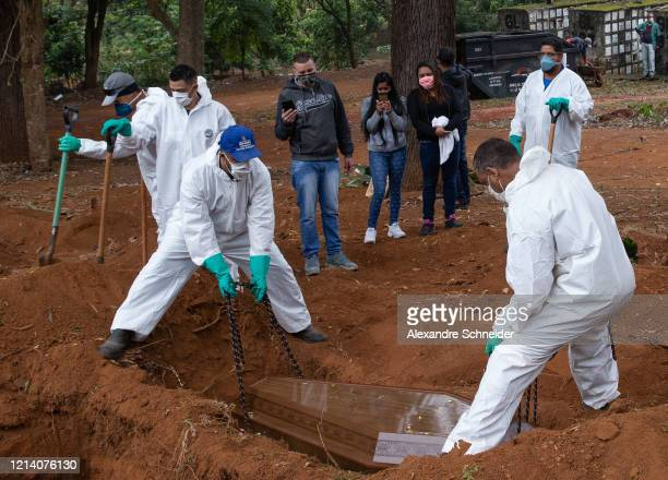 Adenilson Souza Costa, 47 years, and his coworkers wearing protective gear bury a coffin during a burial at Vila Formosa Cemetery amidst the...