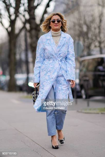 Adenorah wears sunglasses a turtleneck a blue coat with white embroidered flowers blue jeans during Paris Fashion Week Womenswear Fall/Winter...