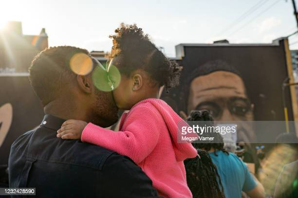 Adeyemi and daughter Adenike listen to people speak before they march through the streets after the verdict was announced for Derek Chauvin on April...