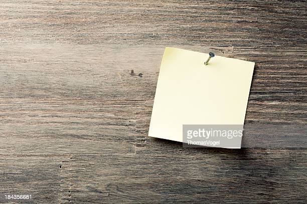 Adhesive note nailed on old wood background
