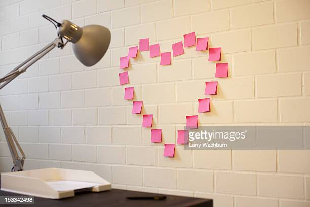 Adhesive notes arranged into the shape of a heart on a wall next to a desk