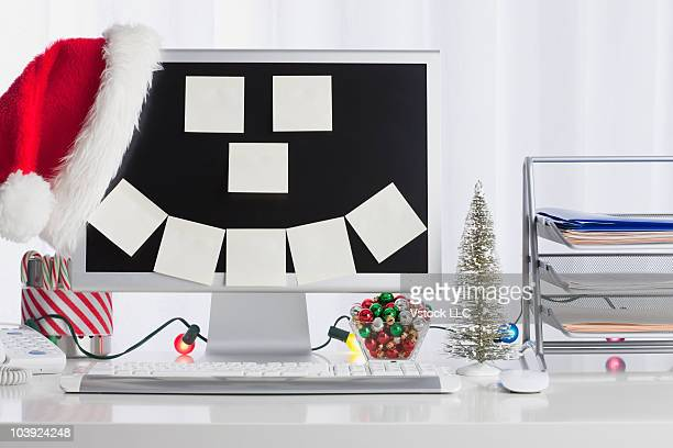 Adhesive notes in shape of happy face stuck to computer