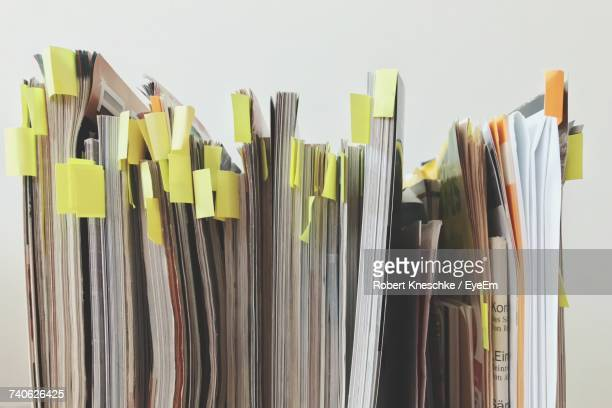 Adhesive Notes On Magazines Against White Wall