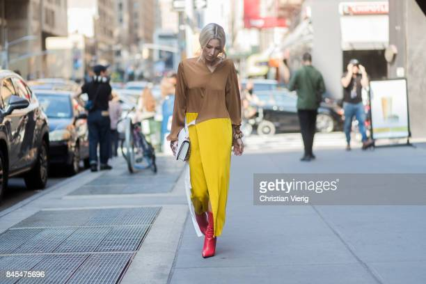 Adi Heyman wearing yellow brown dress with slit seen in the streets of Manhattan outside Sies Marjan during New York Fashion Week on September 10...