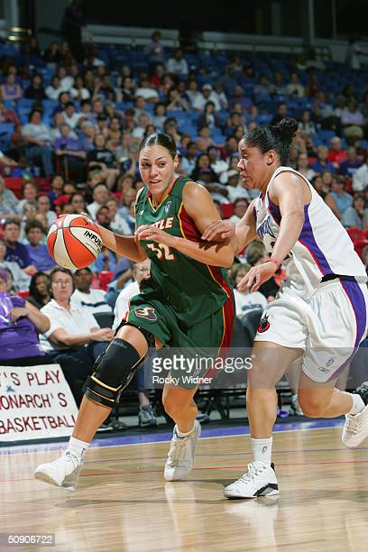 Adia Barnes of the Seattle Storm drives around Kara Lawson of the Sacramento Monarchs during the preseason game at Arco Arena on May 14 2004 in...