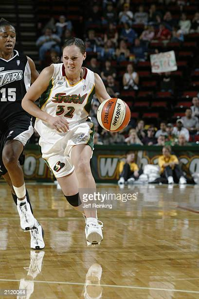 Adia Barnes of the Seattle Storm drives past Adrienne Goodson of the San Antonio Silver Stars during the game on June 22 2003 at Key Arena in Seattle...