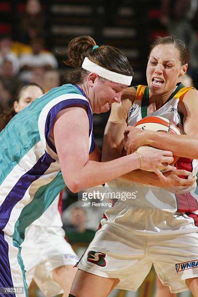 Adia Barnes of the Seattle Storm fights for the ball with Summer Erb of the Charlotte Sting during the game at Key Arena in Seattle Washington on...