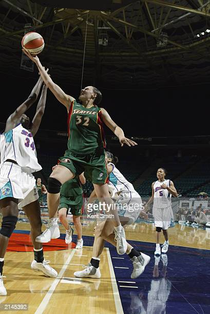 Adia Barnes of the Seattle Storm lays a shot up over Rushia Brown of the Charlotte Sting during the game on June 30 2003 at Charlotte Coliseum in...
