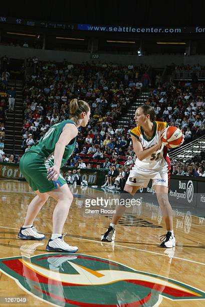 Adia Barnes of the Seattle Storm looks to pass against Katie Smith of the Minnesota Lynx on July 31 2002 at Key Arena in Seattle Washington The Storm...