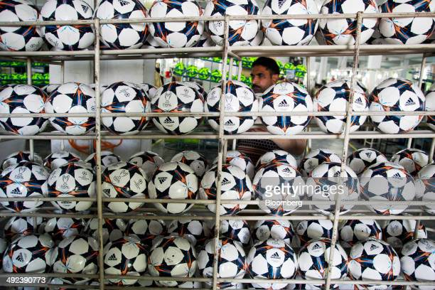 Adidas AG 'Capitano Replica' soccer balls sit in a rack at the Forward Sports Ltd factory in Sialkot Punjab Pakistan on Tuesday Jan 28 2014 Pakistan...