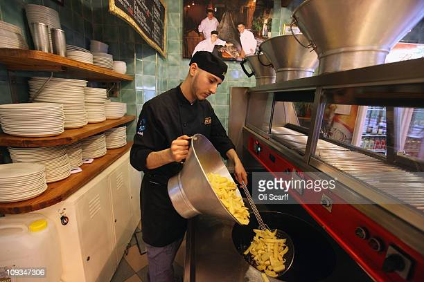 Adil Niazi fries chips in the preparation of a traditional portion of fish and chips in Olley's fish restaurant on February 22 2011 in London England...