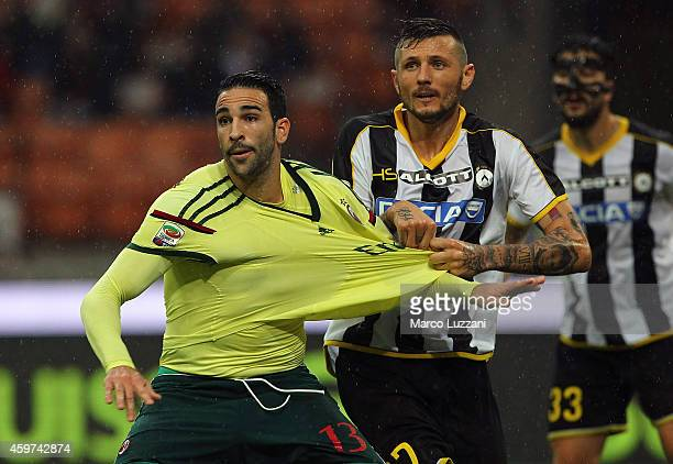 Adil Rami of AC Milan is pulled by his shirt by Cyril Thereau of Udinese Calcio during the Serie A match between AC Milan and Udinese Calcio at...