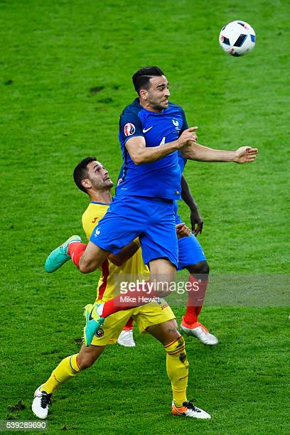 Adil Rami of France and Florin Andone of Romania compete for the ball during the UEFA Euro 2016 Group A match between France and Romania at Stade de...