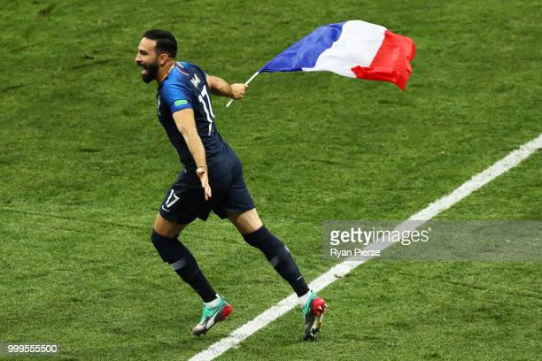 Adil Rami of France celebrates victory displaying the French flag following the 2018 FIFA World Cup Final between France and Croatia at Luzhniki...