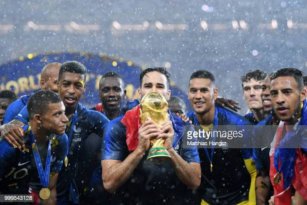 Adil Rami of France celebrates with the World Cup trophy with team mates following the 2018 FIFA World Cup Final between France and Croatia at...