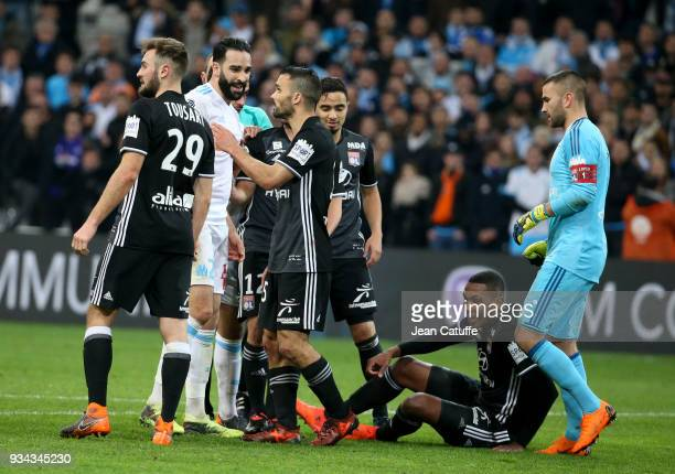 Adil Rami of OM is restrained by Jeremy Morel of Lyon while Marcelo Guedes of Lyon sits on the pitch and goalkeeper of Lyon Anthony Lopes looks on...