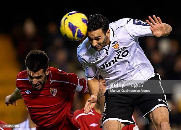 Adil Rami of Valencia competes for the ball with Alvaro Negredo of Sevilla during the La Liga match between Valencia and Sevilla at Estadio Mestalla...