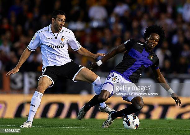 Adil Rami of Valencia competes for the ball with Manucho of Real Valladolid during the La Liga match between Valencia CF and Real Valladolid CF at...