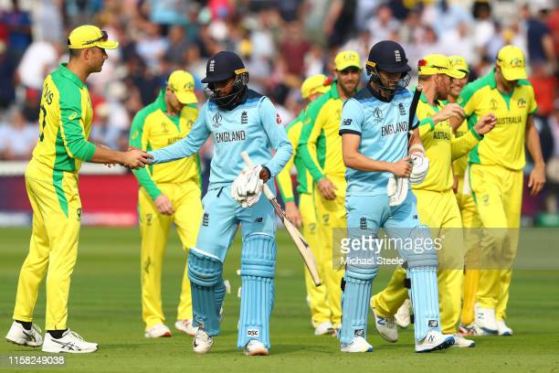 Adil Rashid alongside Mark Wood of England shakes hands with Marcus Stoinis of Australia after England's 64 run defeat during the Group Stage match...