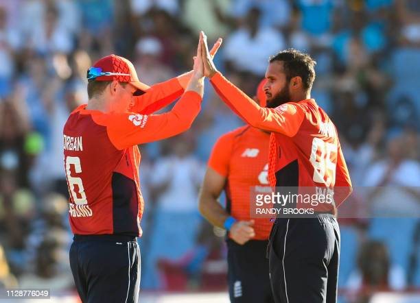 Adil Rashid and Eoin Morgan of England celebrate the dismissal of Carlos Brathwaite of the West Indies during a T20 match between the West Indies and...