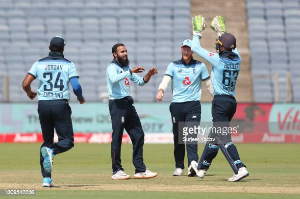 Adil Rashid of England celebrates after taking the wicket of Shikhar Dhawan of india with team mates Chris Jordan, Jos Buttler and Ben Stokes during...