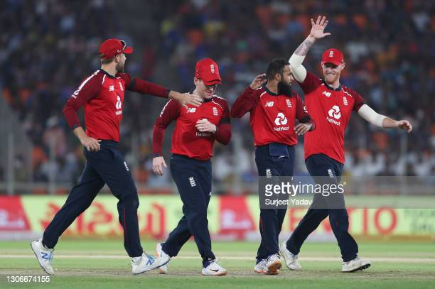 Adil Rashid of England celebrates after taking the wicket of Virat Kohli of India with team mates Dawid Malan, Eoin Morgan and Ben Stokes during the...