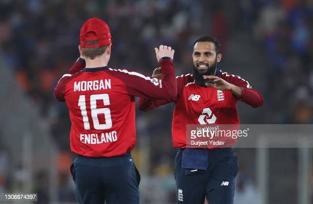 Adil Rashid of England celebrates after taking the wicket of Virat Kohli of India with team mate Eoin Morgan during the 1st T20 International match...