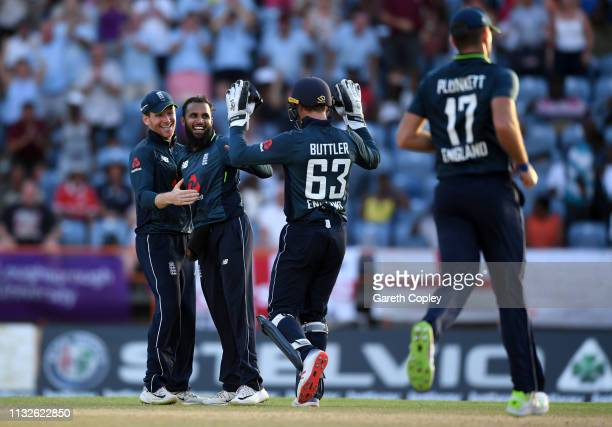 Adil Rashid of England celebrates with Eoin Morgan and Jos Buttler after taking the final wicket of Oshane Thomas of the West Indies to win the 4th...