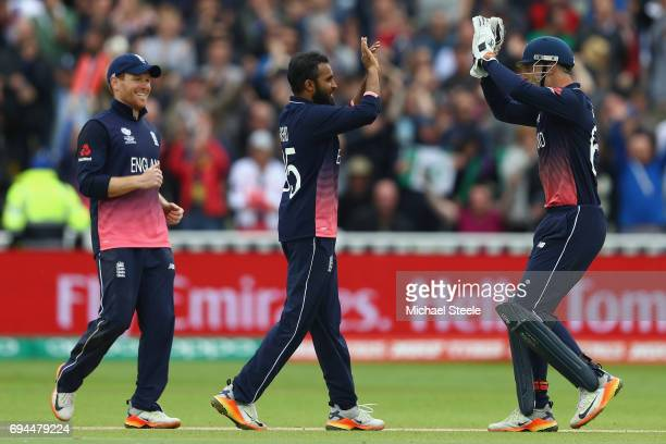 Adil Rashid of England celebrates with Jos Buttler and Eoin Morgan after taking the wicket of Mitchell Starc during the ICC Champions Trophy match...