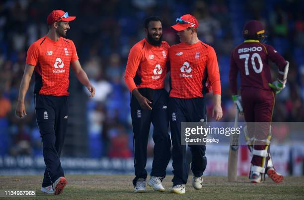 Adil Rashid of England celebrates with Mark Wood and Eoin Morgan after dismissing Obed McCoy of the West Indies during the 3rd Twenty20 International...