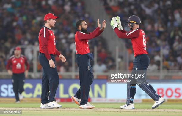 Adil Rashid of England celebrates with team mates Jason Roy and Jos Buttler after taking the wicket of Ishan Kishan of India during the 2nd T20...