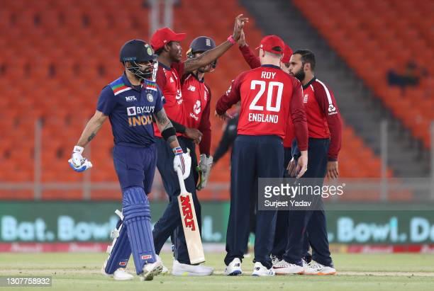 Adil Rashid of England celebrates with teammates after dismissing India captain Virat Kohli during the 4th T20 International between India and...